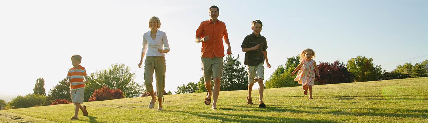 Healthy family running down grassy slope